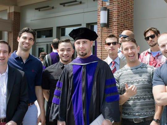 In this May 9, 2015 photo provided by the UNC School of Law Jamey Anderson, center, poses during his commencement ceremony in Chapel Hill, N.C. With him are fellow former Word of Faith Fellowship members Peter Cooper, second left blue shirt; Ben Carmona, third left; Jay Plummer, tan suit; John Blanton, red plaid shirt and sunglasses, and other friends.