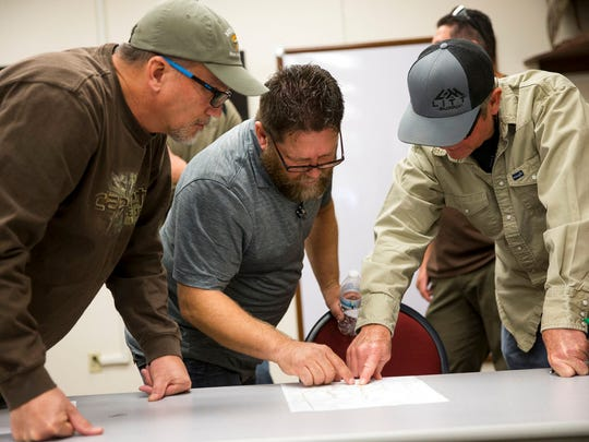 In this Friday, Dec. 15, 2017 photo, John Harris, from left, of Henderson, Dave Raynor, of Boulder City, and Darrel Leavitt, of Las Vegas, attend an orientation at the Clark County Shooting Complex for hunters randomly picked for the annual bighorn sheep hunt inside the Nevada Test and Training Range in Las Vegas.