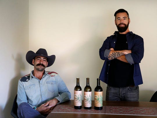 In this Friday, Dec. 22, 2017, photo, Alex Howe, right, and Chip Forsythe, co-founders of Rebel Coast, pause for photos with their cannabis-infused wine in Los Angeles.