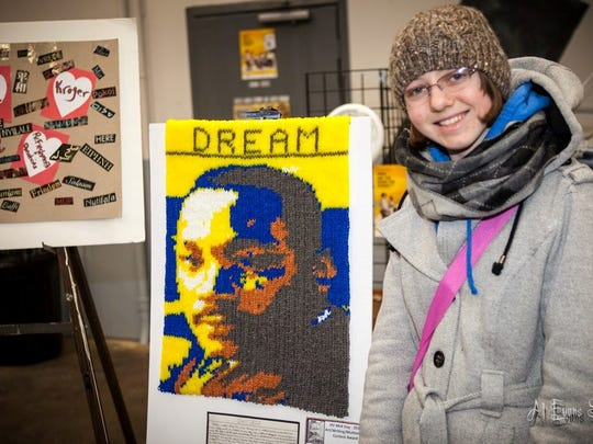 Meredith Jeffery, a previous art contest winner in the 12-17 age group, shows off her work.