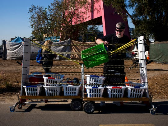 "Joel Sheehan, who does free laundry for homeless people living on the Santa Ana River trail, delivers washed clothes in baskets, each labeled with an individual's name, Tuesday, Dec. 19, 2017, in Anaheim, Calif. ""I do it because I'm grateful for what was done for me at the cross. And this is what my gratitude looks like,"" said Sheehan. ""They were able to go to stores with dignity because they didn't stink."""