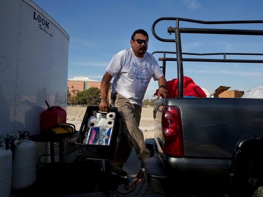 "Armando Olvera, 49, who has been providing mobile showers for the homeless since 2010, gives out rolls of toilet paper to homeless people while operating a shower trailer on the Santa Ana River trail Saturday, Dec. 2, 2017, in Anaheim, Calif. ""How long I can do this? Forever,"" said Olvera whose day job is a plumber. Goodhearted neighbors heartbroken over the rising number of homeless in their communities are dishing out hot meals, providing mobile showers and handing out sandwiches to those in need, hoping they can make a difference."