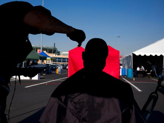 A homeless man, who declined to give his name, gets a free haircut in the parking lot of Angel Stadium during the community outreach day Tuesday, Dec. 19, 2017, in Anaheim, Calif. The event was organized by non-profit organizations and agencies to offer services to homeless people in Orange County.