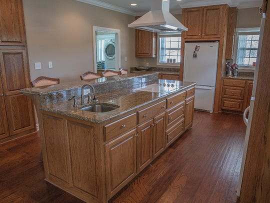 The kitchen has granite counter tops, pull outs in