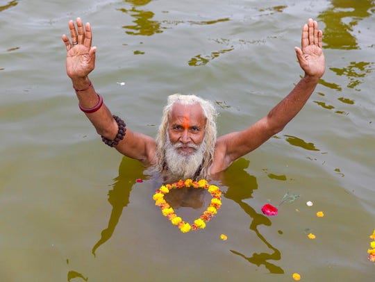 A Hindu holy man offers prayers after taking ritualistic