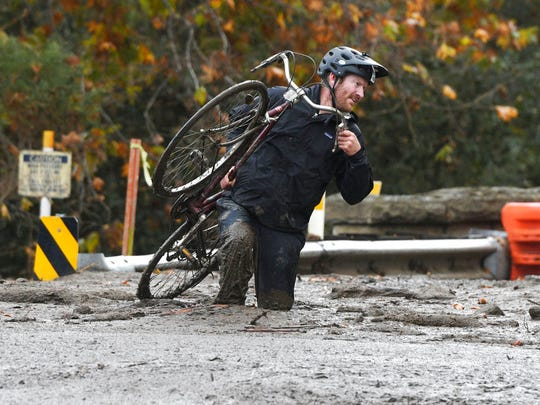 Carpinteria resident Jeff Gallup carries his bike through mud on Foothill Road in Carpinteria, Calif., Tuesday, Jan. 9, 2018. Homes were swept from their foundations as heavy rain sent mud and boulders sliding down hills stripped of vegetation by Southern California's recent wildfires