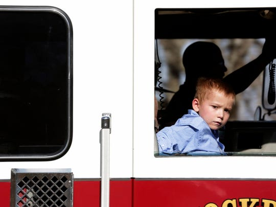 Ryland Ward, who was shot several times in the Sutherland Springs massacre, rides in a Stockdale firetruck with Rusty Duncan, the firefighter who rescued him, in Sutherland Springs, Texas, Jan. 11, 2018.