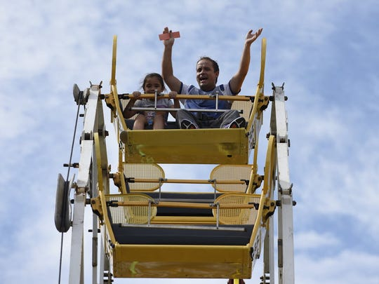 At the 2016 Great Falls Festival at Paterson Great Falls National Historical Park. (right) Ramon Arango, of West New York, and his daughter Guadalupe, 7, ride a ferris wheel.