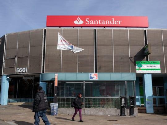 Pedestrians pass a now-closed Santander Bank branch