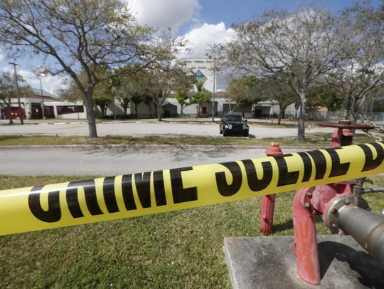 Crime scene tape runs outside Marjory Stoneman Douglas