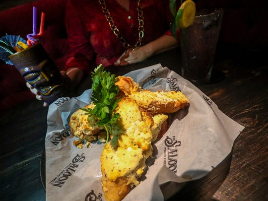 """The Saloon's famous Bubble Bread is a classic italian ciabbatta bread smeared with seven cheeses and accented with garlic and herbs, then baked until it """"bubbles."""""""