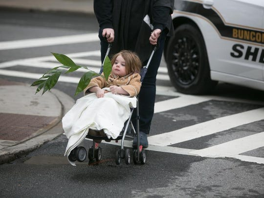 Layla Burnette; age 2, is pushed in a stroller as Central United Methodist Church celebrated Palm Sunday on Sunday, March 25th.  The church held two services and joined with members of First Presbyterian Church and Trinity Episcopal Church for their annual procession to Pritchard Park with two donkeys.