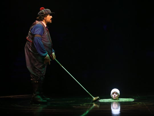 "The Giant Clown (Victorino Lujan) tees up to hit a golf ball (Marie-Christine Menard-Bergeron) that has its own ideas during Cirque du Soleil's performance of ""Corteo."""