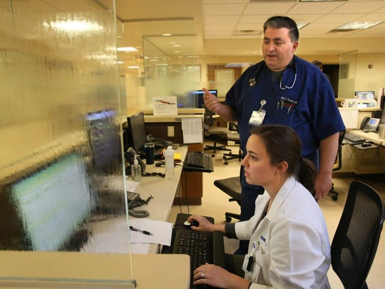 Mark Polentini and Kathryn Hughes, both doctors at Waukesha Memorial Hospital, work in the emergency department.