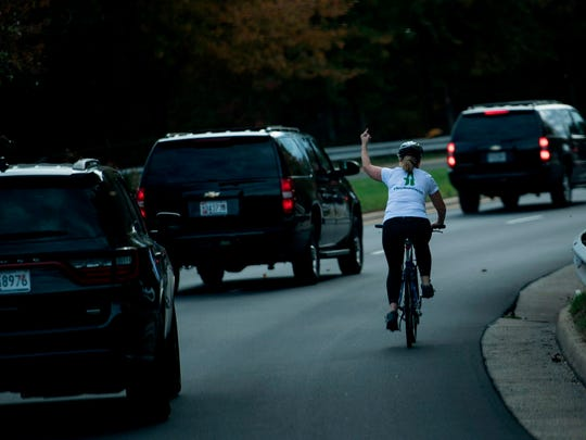 Juli Briskman gestures with her middle finger as a motorcade with President Donald Trump departs Trump National Golf Course in Sterling, Va., Oct. 28, 2017.