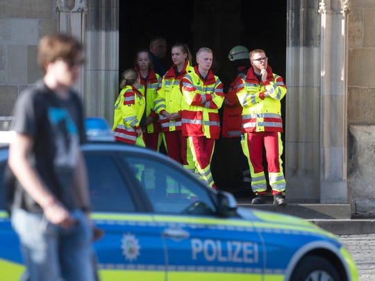 Rescuers stand in downtown Muenster, Germany, Saturday, April 7, 2018. A vehicle crashed into a crowd Saturday in the western German city of Muenster, killing three people and injuring 20 others. The German news agency dpa has quoted police as saying the driver of that car in Muenster has killed himself.  (Bernd Thissen/dpa via AP)
