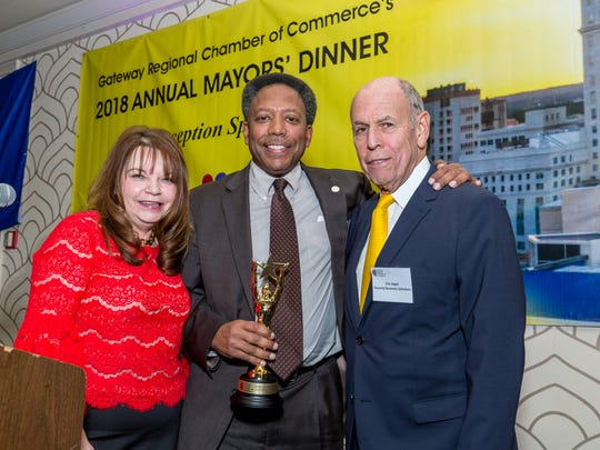 Linden Mayor Derek Armstead (center), named Mayor of the Year at the 2018 Mayors' Dinner of the Gateway Regional Chamber of Commerce, is congratulated by Angie Tsirkas of Northfield Bank and Eric Segal of Security Business Solutions.