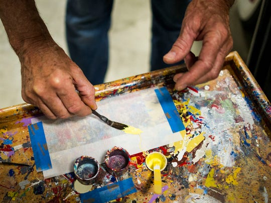 Alex Olivera wipes away excess paint from his brush before painting a car at a shop in Naples on Wednesday, March 28, 2018.
