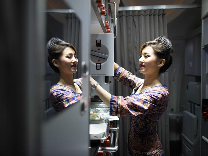 A flight attendant prepares meals for passengers aboard