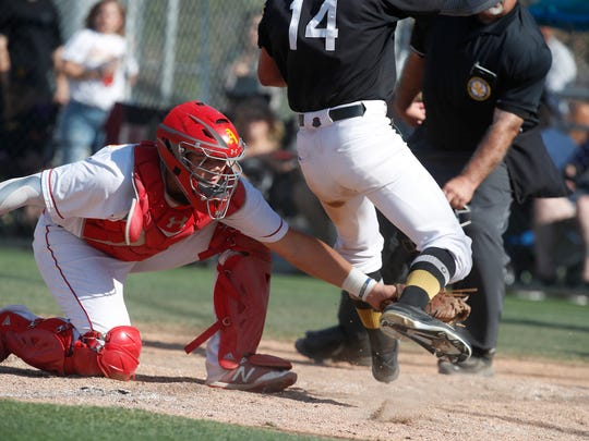 Palm Desert High School's Sammy Garcia applies a tag at home against Capistrano Valley in the first round CIF game at Palm Desert. Capistrano won 4-0.