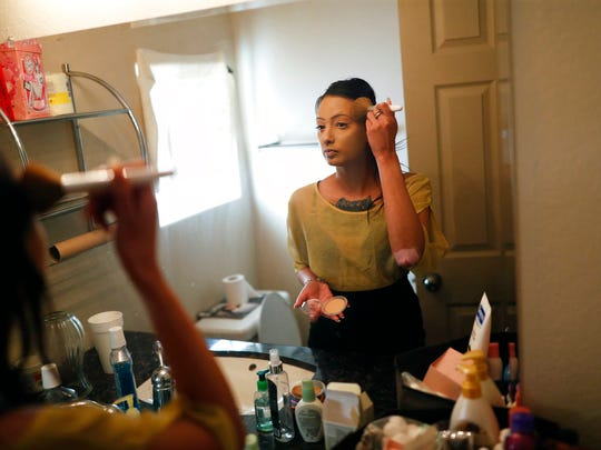 In this April 27, 2018, photo, prostitute Destini Starr applies makeup in her bathroom at the Love Ranch brothel in Crystal, Nev. A coalition of religious groups and anti-sex trafficking activists have launched referendums to ban brothels in two of Nevada's seven counties where they legally operate. (AP Photo/John Locher)
