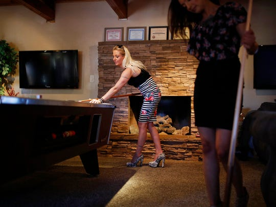 "In this June 1, 2018, photo, prostitutes Destini Starr, right, and Paris Envy play pool while waiting for customers at the Love Ranch brothel in Crystal, Nev. A coalition of religious groups and anti-sex trafficking activists have launched referendums to ban brothels in two of Nevada's seven counties where they legally operate. Legal pimp Dennis Hof, who has half a dozen brothels operating in the two counties and starred in the HBO adult reality series ""Cathouse,"" is challenging incumbent Assembly member James Oscarson of Pahrump in a Republican primary Tuesday, June 12. (AP Photo/John Locher)"