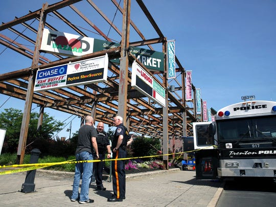 Police stand near an industrial area outside the warehouse building where the Art All Night Trenton 2018 festival was the scene of a shooting that resulted in numerous injuries and at least one death Sunday, June 17, 2018, in Trenton, N.J.