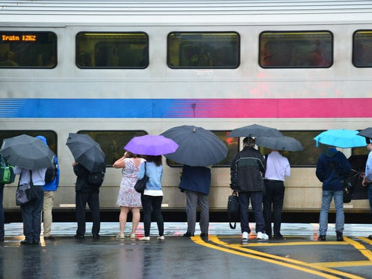 Commuters use umbrellas to shield themselves from the