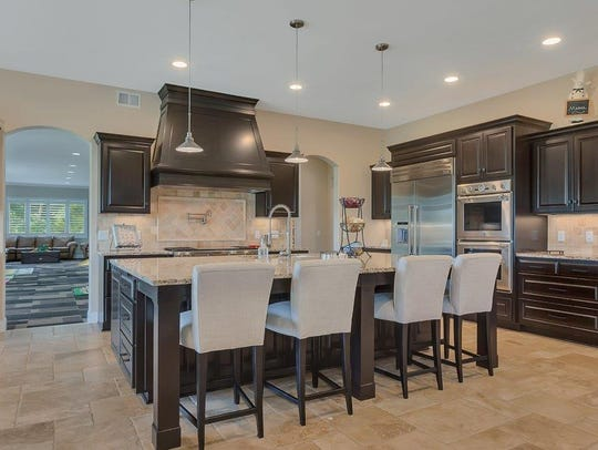The kitchen includes travertine floors, granite countertops,