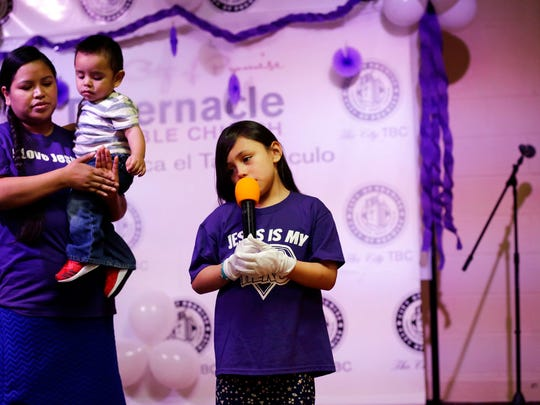 Holding her youngest son, Alma Vazquez stands next