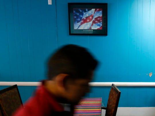 A man walks by a framed poster of a U.S. flag inside