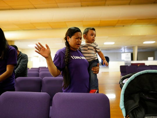 Alma Vazquez prays as she holds one of her five children