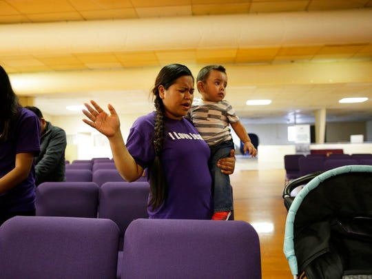 Alma Vazquez prays as she holds one of her five children at the Tabernacle Bible Church in Fairfield, Ohio, on April 28, 2018. Her husband, Brandon Tomas Tomas, was arrested by an ICE agent looking for someone else at the warehouse where he worked, and now faces likely deportation. (AP Photo/Gregory Bull)
