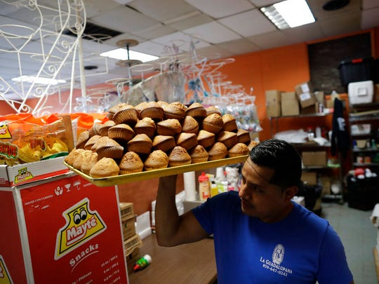 Oscar Gonzalez carries freshly baked bread in his store, La Guadalupana, in Florence, Ky., on April 27, 2018. La Guadalupana is a focal point of the Latino immigrant community in northern Kentucky, which has grown to several thousand over the last three decades. (AP Photo/Gregory Bull)