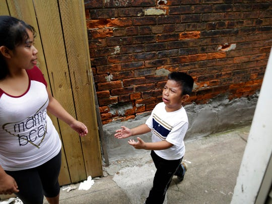 """Carmelinda Perez tries to sooth her crying son, Franco, after he ran out of the house looking for his father in Florence, Ky., on April 28, 2018. """"We continue with fear,"""" says his father, who was among roughly two dozen people arrested during and immediately after the operation. (AP Photo/Gregory Bull)"""