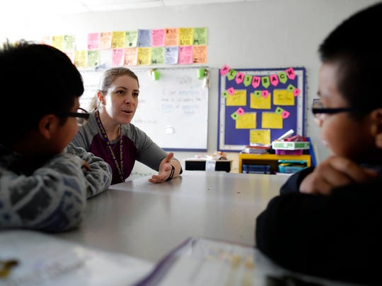 School social worker Kerry McHugh talks to children at John G. Carlisle Elementary School in Covington, Ky., on April 27, 2018. McHugh and other people who work in northern Kentucky schools have had to respond to families in crisis after losing a parent in the raid. (AP Photo/Gregory Bull)