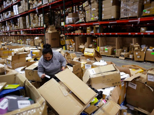 An employee sorts through boxes at the Win.It America warehouse in Walton, Ky., on May 1, 2018. After an ICE agent arrested one of the company's employees, the warehouse lost 28 workers over several weeks and struggled to meet its shipping deadline. (AP Photo/Gregory Bull)