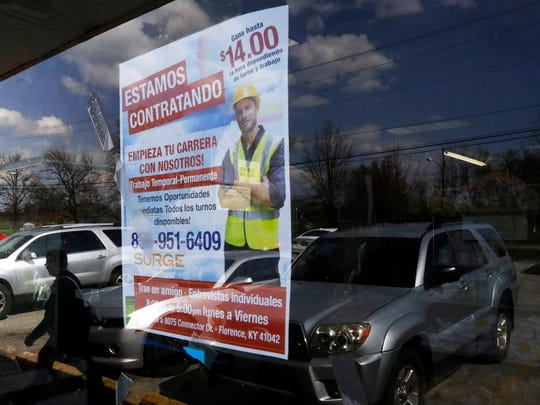 A poster announcing available jobs hangs in the window of the store La Guadalupana in Florence, Ky., on April 27, 2018. The manager of one warehouse says immigrant workers are prized for their work ethic and reliability. (AP Photo/Gregory Bull)