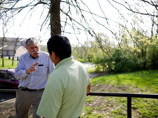 """Don Sherman of the local Immigrant Dignity Coalition talks to a Guatemalan immigrant outside a home in Florence, Ky., on May 1, 2018. """"We don't know what's going to happen in the future,"""" Sherman says. """"We're doing what is like a triage ... and there's still a lot of suffering."""" (AP Photo/Gregory Bull)"""