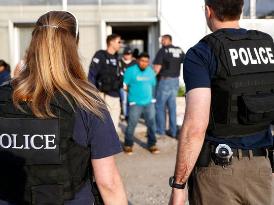 FILE - In this June 5, 2018 file picture, government agents detain suspects during an immigration raid in Castalia, Ohio. Regular raids are a key part of President Donald Trump's administration's crackdown on immigrants living in the U.S. illegally. (AP Photo/John Minchillo, File)