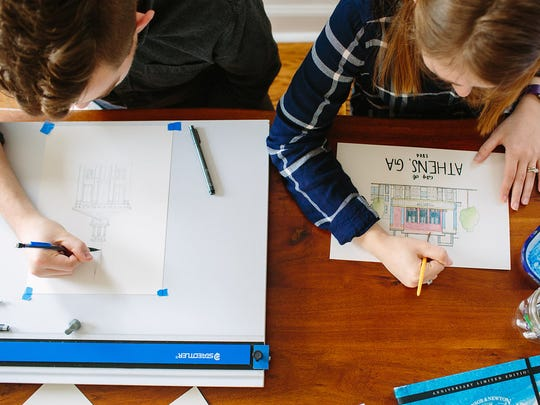 Logan Higgins (left) and wife Katherine Higgins work in their JFG Flats apartment to sketch and color in architectural drawings for their new business, Jacks Avenue.