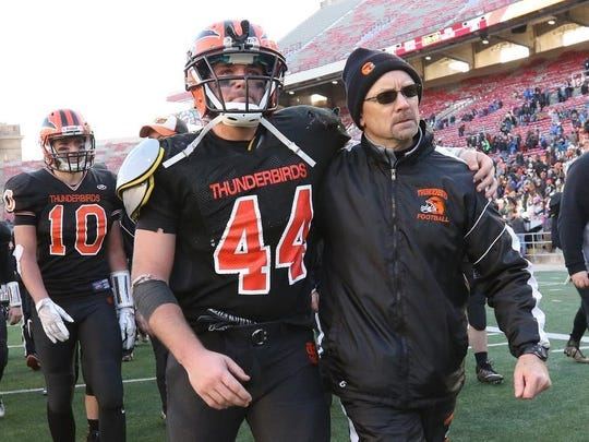 Iola-Scandinavia coach Scott Erickson, right, embraces Bryce Huettner as they walk off the field at Camp Randall Stadium in Madison after falling to St. Mary's Springs in the Division 6 state title game last season.