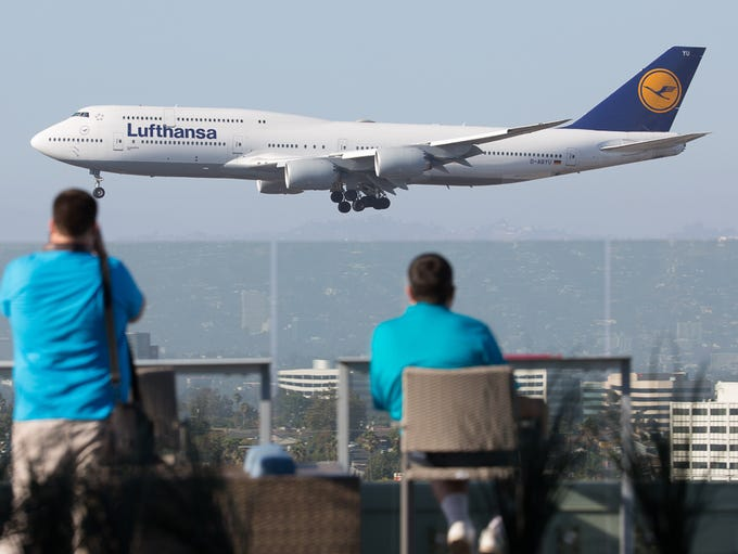Plane spotters watch a Boeing 747-8i land at Los Angeles