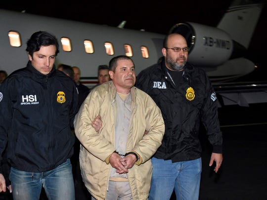 "This file photo shows federal authorities escorting alleged Mexican drug kingpin Joaquin ""El Chapo"" Guzman, center, from a plane to a waiting caravan of government SUVs after he was extradited to the U.S. to stand trial on drug conspiracy charges."
