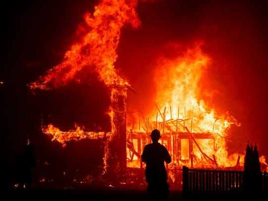 In this Nov. 8, 2018, file photo, a home burns as the Camp Fire rages through Paradise, Calif. California wildland managers announced a plan to speed up logging and prescribed burns designed to protect communities from wildfires, at a news conference Tuesday, Jan. 29, 2019. The effort would create a single environmental review process to cover vegetation reduction projects, field breaks and restoration projects.
