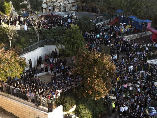 Mourners attend the funeral services late in the afternoon