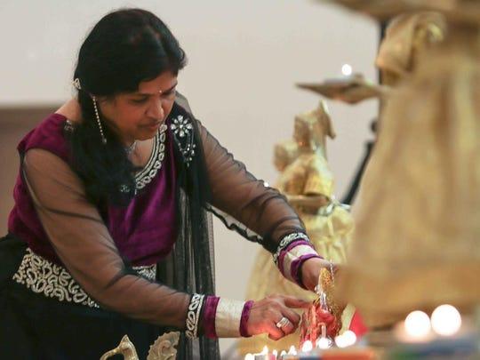 Kashmira M, Patel decorates the statue Amba Ma prior to Diwali festivities Sunday, Oct 12, 2014 at the Nur Shrine in New Castle.