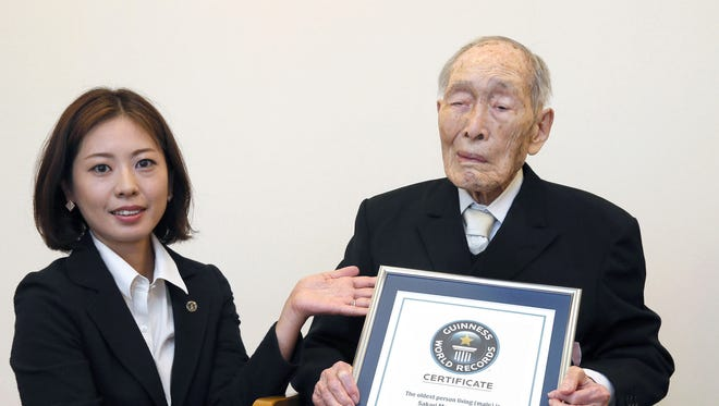 Sakari Momoi, a 111-year-old Japanese retired educator, poses for a photo after receiving a certificate from a Guinness World Records official, left, in Tokyo on Wednesday, Aug. 20, 2014. Momoi was recognized as the world's oldest living man.
