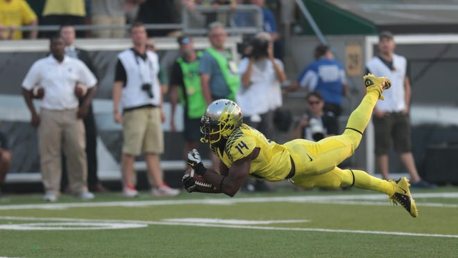 Sep 6, 2014; Eugene, OR, USA; Oregon Ducks defensive back Ifo Ekpre-Olomu (14) dives for an interception against the Michigan State Spartans at Autzen Stadium. Mandatory Credit: Scott Olmos-USA TODAY Sports