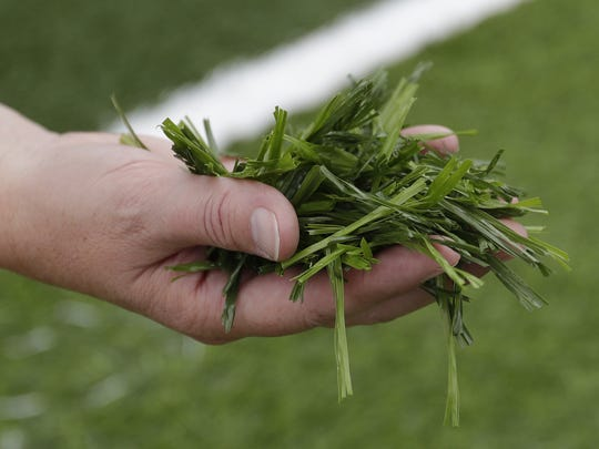 Pulaski High School Athletics Director Janel Batten holds a handful of artificial grass as she tours the new Saputo Stadium at Pulaski High School. The Field of Dreams initiative funded the new stadium and artificial turf field.
